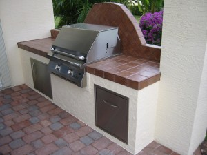 Built in solaire infrared gas grill in grill island with lp tank drawer and single built in access door.