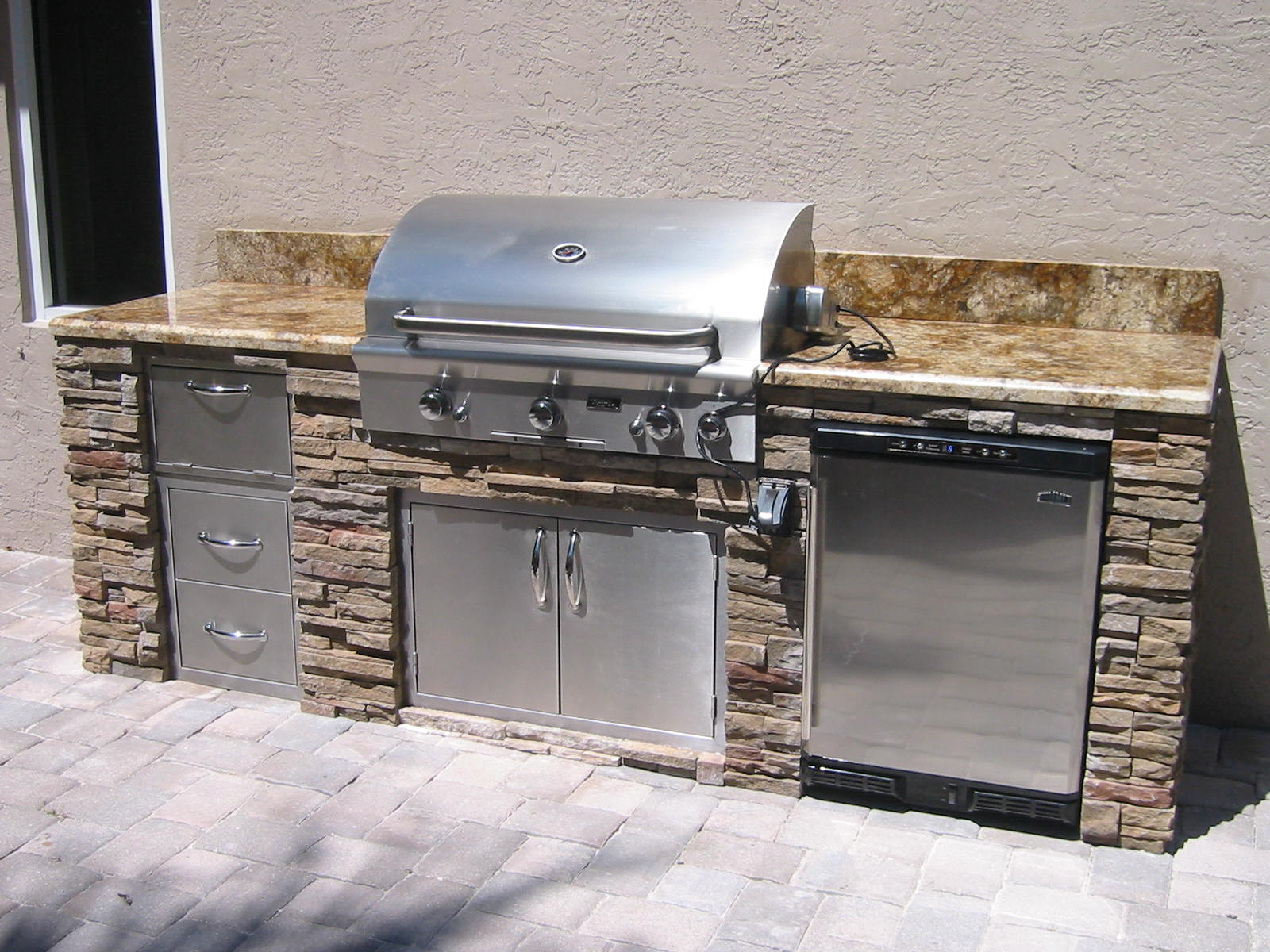 outdoor kitchen with built in AOG grill by RH Peterson